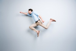 Happy, attractive, handsome, young, cool, joyful man with bristle jumping in air showing superman pose over grey background