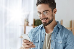 Happy attractive male European model looks happily at mobile phone, reads positive news from newsfeed, sends message to lover during work break. Young man recieves email on modern smart phone