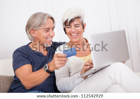 Happy attractive middle-aged couple making an online purchase or booking using a credit card on their laptop