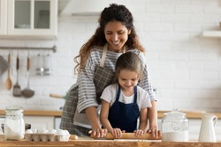 Happy attractive mommy helping cute smiling little preschool child daughter rolling dough for homemade pastry. Excited two female generations family enjoying cooking process together in kitchen.