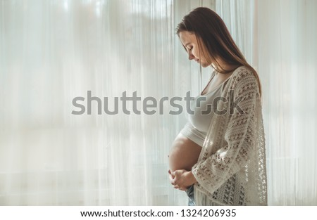 Happy Attractive pregnant woman standing near the window and holding her belly. Concepts of pregnancy and family