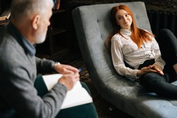 Happy attractive redhead young woman patient is telling about her mental health while lying in comfortable sofa during psychological consultation. . Concept of psychological treatment.