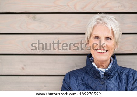 Happy attractive senior lady standing against a wooden clad building smiling at the camera with copyspace alongside