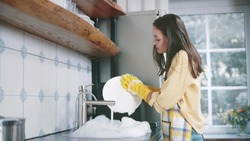 Happy attractive woman in apron and gloves washing dishes at home kitchen. Side view of pretty young housewife doing household. Beautiful female wash plates