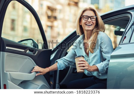 Happy attractive woman or business lady wearing eyeglasses holding cup of coffee and getting out of her modern car