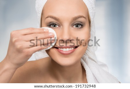 Happy attractive women removing makeup in the bathroom