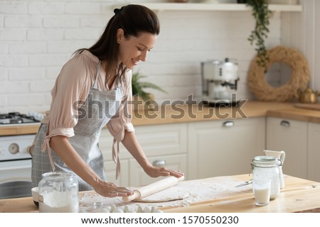 Happy attractive young adult woman lady housewife baker wear apron holding pin rolling dough on kitchen table baking pastry concept cooking cake biscuit doing bakery making homemade pizza at home