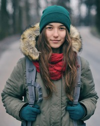 Happy attractive young girl wearing warm clothing. Lonely girl with backpack standing in forest or park. Single woman alone walking on snow covered road through alley of trees. Enjoying fresh air