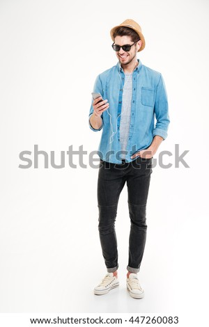 Happy attractive young man in hat and sunglasses listening to music from smartphone over white background stock photo
