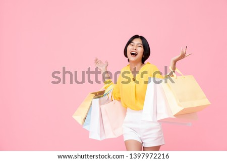 Happy attractive young thai asian female carrying pastel colored shopping bags with both arms raised in a ecstatic gesture isolated in pink studio background