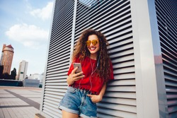 Happy attractive young woman in sunglasses listening to music in earphones, looking at smartphone screen while walking in the city. Dressed in stylish clothes.