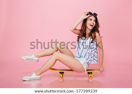 Happy attractive young woman in sunglasses sitting on skateboard over pink background