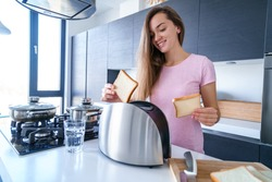 Happy attractive young woman using toaster for making breakfast toast in the kitchen at home early in the morning. Household and kitchen appliance for cooking food