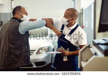 Happy auto mechanic and his manager elbow bumping and wearing protective face masks in a workshop during coronavirus pandemic.  Photo stock ©
