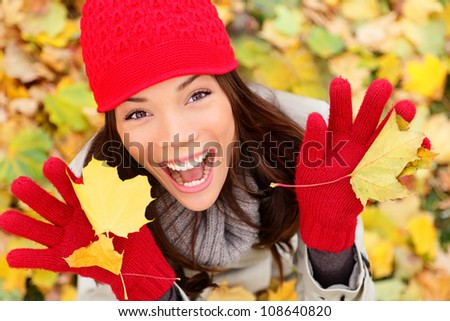 Happy autumn woman playing in leaves. utumn portrait of happy lovely and beautiful mixed race Asian Caucasian young woman in forest in fall colors. #108640820