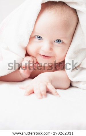 Happy baby after bathing, looks with white towels, funny smiles and looks into the camera