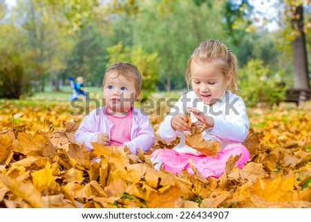 Happy baby and little girl have fun with autumn leaves in the park.