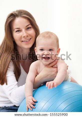 Happy baby boy and his mother playing with large ball