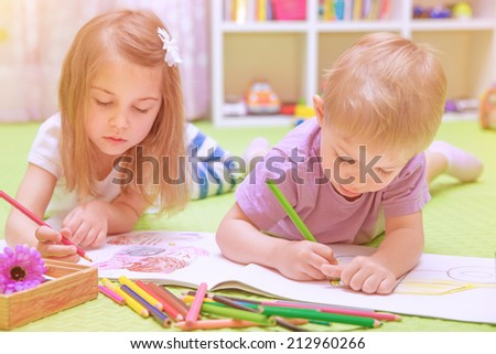 Happy baby boy & girl enjoying homework, preschool developing drawing skills, talented children learning art, kids back to school concept