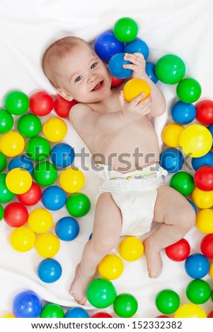 Happy baby boy in diapers with lots of colorful balls playing