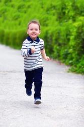 happy baby boy in motion, running the spring street