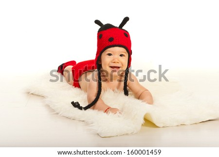 Happy baby boy laying and wearing funny ladybug hat
