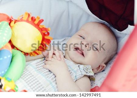 happy baby boy laying in pram