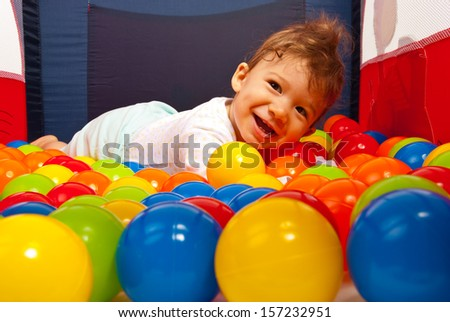 Happy baby boy lying on colorful balls in playpen