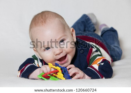 Happy baby boy lying on his stomach and playing with toy and smiling.