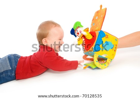 Happy baby boy (6 months old) playing with soft toys, smiling. Toys are property released.?