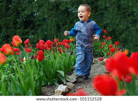 happy baby boy running the flower garden