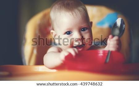 Happy baby boy spoon eats itself