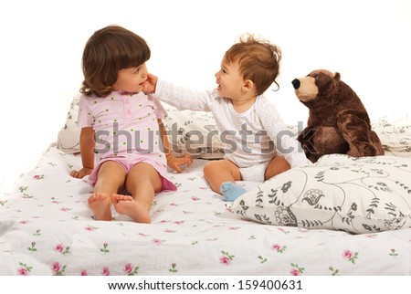 Happy baby boy touching toddler girl face in bed