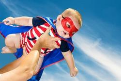 Happy baby boy wearing superhero costume flying in the sky