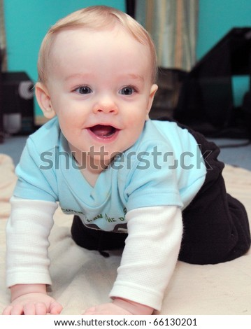 Happy baby boy with blonde hair and blue eyes crawls on floor with huge grin on his cute little face