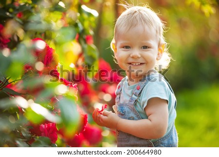 Happy baby boy with red roses in summer garden