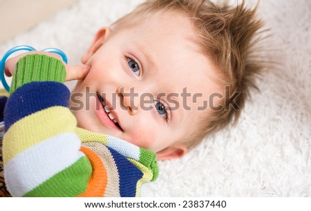 Happy baby boy ( 2 years old ) lying on back looking up to camera, smiling.