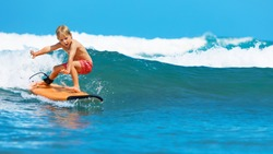Happy baby boy - young surfer learn to ride on surfboard with fun on sea waves. Active family lifestyle, kids outdoor water sport lessons, swimming activity in surf camp. Summer vacation with child.