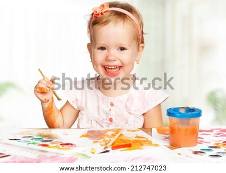 happy baby child girl draws paints