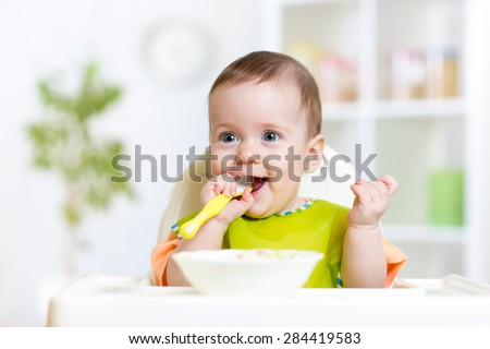 happy baby child sitting in chair with a spoon