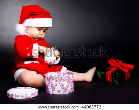 happy baby dressed as Santa opening the christmas presents
