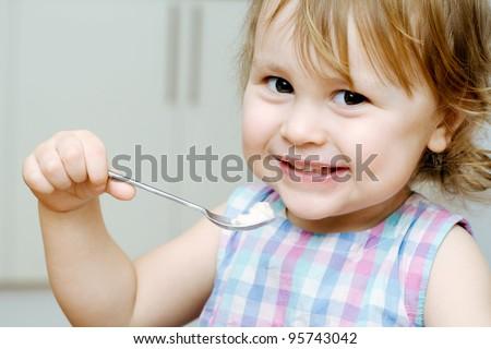 Happy baby eating porridge with spoon - stock photo