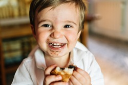 Happy baby eats sweet chocolate cake. He wears a white summer shirt and is sitting in his highchair to eat. Children's concept