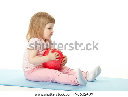 Happy baby girl doing exercises with a ball sitting on a mat; white background