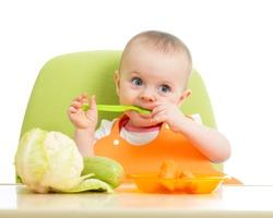 happy baby girl eating vegetables