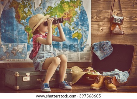 Shutterstock happy baby girl getting ready for the journey. Girl packs her bags and playing with binoculars.