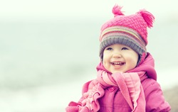 Happy baby girl in a pink hat and scarf laughs