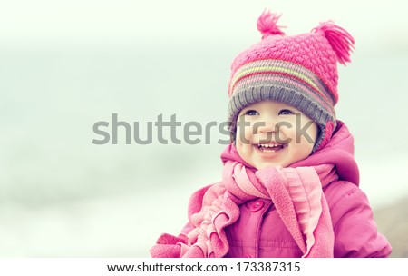 Stock Photo Happy baby girl in a pink hat and scarf laughs