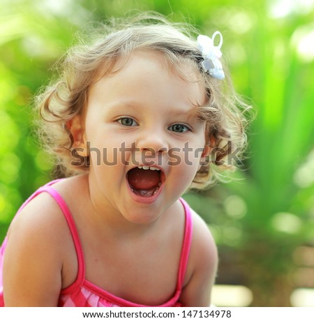 Happy baby girl joy with opened mouth outdoor summer background. Closeup