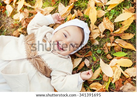 Stock Photo Happy baby girl laying on autumn leaves